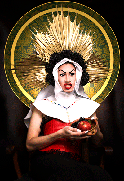 Fotografia de una drag queen vestida al estilo de una monja con un gran tocado dorado con flores negras en la cabeza y sostiendo una vasija con una manzana y unas uvas.